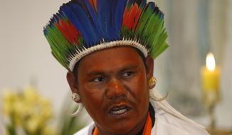 Surui, a Pataxo Indigenous chieftain, with his face painted red to represent fellow indigenous people that have been killed, speaks at the launch of a report on violence against indigenous peoples in Brazil, at the headquarters of the National Conference of Bishops in Brasilia, Brazil, Tuesday, Sept. 24, 2019. A Brazilian Catholic Church agency says invasions of indigenous lands have jumped in the first nine months of President Jair Bolsonaro administration. The Missionary Indigenous Council said Tuesday that illegal miners, loggers and tappers of natural resources are involved in most of the invasions. (AP Photo/Eraldo Peres)