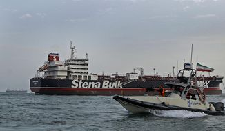 In this July 21, 2019, file photo, a speedboat of the Iran's Revolutionary Guard moves around a British-flagged oil tanker Stena Impero, which was seized on Friday by the Guard, in the Iranian port of Bandar Abbas. A ship-tracking website shows a British-flagged oil tanker held by Iran since July moving for the first time in weeks. The movement of the Stena Impero on Tuesday, Sept. 24,  comes after a government spokesman in Iran on Monday said legal proceedings against the vessel had concluded.(Hasan Shirvani/Mizan News Agency via AP, File)
