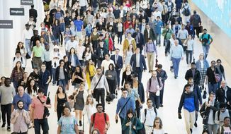 In this June 21, 2019, file photo commuters walk through a corridor in the World Trade Center Transportation Hub in New York. Millennial workers are more likely than older generations to report being burned out at work, according to a 2018 Gallup study. (AP Photo/Mark Lennihan, File)