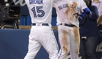 Toronto Blue Jays' Anthony Alford celebrates his walk-off home run with teammate Randal Grichuk to end the ballgame in the 15th inning against the Baltimore Orioles, Monday, Sept. 23, 2019, in Toronto. Toronto won 11-10. (Fred Thornhill/The Canadian Press via AP)