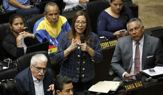 Lawmakers Tania Diaz of the Venezuelan Socialist United Party speaks during a National Assembly session in Caracas, Venezuela, Tuesday, Sept. 24, 2019. Lawmakers with the ruling socialist party returning to the National Assembly Tuesday after years of absence as part of a widely criticized pact between President Nicolas Maduro and a handful of outlier opposition parties. Opposition leader Juan Guaido is the legislature's president and has lambasted the accord. (AP Photo/Ariana Cubillos)