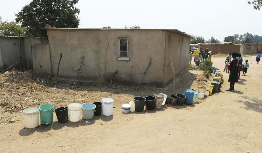 Buckets are seen in a queue to fetch water at a borehole in Harare, Tuesday, Sept, 24, 2019. The more than 2 million residents of Zimbabwe's capital and surrounding towns are now without water after authorities shut down the city's main treatment plant, raising new fears about disease after a recent cholera outbreak while the economy crumbles further. (AP Photo/Tsvangirayi Mukwazhi)