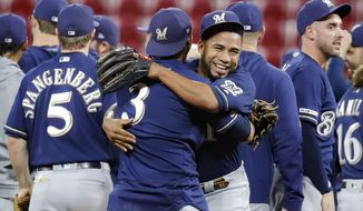 Milwaukee Brewers relief pitcher Junior Guerra, center right, celebrates with shortstop Orlando Arcia (3) after the team's 9-2 win over the Cincinnati Reds in a baseball game Wednesday, Sept. 25, 2019, in Cincinnati. (AP Photo/John Minchillo) ** FILE **
