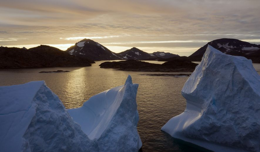 This early Friday, Aug. 16, 2019, file photo shows an aerial view of large Icebergs floating as the sun rises near Kulusuk, Greenland. (AP Photo/Felipe Dana) ** FILE **