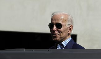 Democratic presidential candidate former Vice President Joe Biden peeks out of the roof of an SUV to speak to reporters as he leaves a fundraiser appearance Wednesday, Sept. 25, 2019, in Manhattan Beach, Calif. (AP Photo/Marcio Jose Sanchez)
