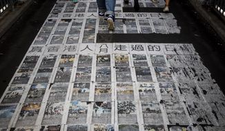 "People walk photos showing the recent protests with words ""The days the Hong Kong people have passed"" at a pedestrian overhead bridge in Hong Kong, Wednesday, Sept. 25, 2019. Hong Kong leader Carrie Lam said Tuesday, Sept. 24 she doesn't expect a town hall meeting this week to find answers to the months-long pro-democracy protests but hopes it will be a step forward in the ""long journey"" to reconciliation. (AP Photo/Vincent Thian)"