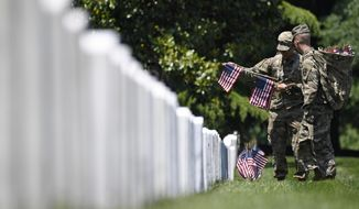 "FILE -In this May 23, 2019 file photo, members of the 3rd U.S. Infantry Regiment, also known as The Old Guard, place flags in front of each headstone for ""Flags-In"" at Arlington National Cemetery in Arlington, Va. The Army is proposing new rules that would significantly restrict eligibility for burial at Arlington National Cemetery in an effort to preserve a dwindling number of gravesites well into the future. (AP Photo/Susan Walsh, File)"