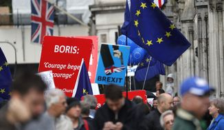 Pro and anti-Brexit supporters hold signs and flags while demonstrating outside the Parliament in London, Wednesday, Sept. 25, 2019. Lawmakers in Britain are returning to the House of Commons on Wednesday, following a Supreme Court ruling that Prime Minister Boris Johnson had acted illegally by suspending Parliament. (AP Photo/Frank Augstein)