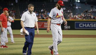 Injured St. Louis Cardinals starting pitcher Michael Wacha, right, walks off the field with head athletic trainer Adam Olsen, middle, as Cardinals pitching coach Mike Maddux, left, looks to the bullpen during the second inning of a baseball game against the Arizona Diamondbacks Wednesday, Sept. 25, 2019, in Phoenix. (AP Photo/Ross D. Franklin)