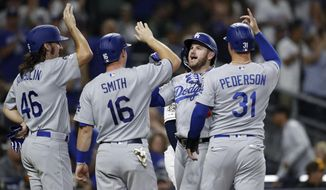 Los Angeles Dodgers' Max Muncy, second from right, greets teammates Tony Gonsolin (46), Will Smith (16), and Joc Pederson (31), after hitting a grand slam during the fourth inning of a baseball game against the San Diego Padres Tuesday, Sept. 24, 2019, in San Diego. (AP Photo/Gregory Bull)