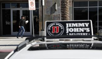 FILE - In this Feb. 6, 2019, photo, Tyler Schwecke, a delivery driver for Jimmy John's, makes a delivery in Las Vegas. The parent company of Arby's and Buffalo Wild Wings is buying Jimmy John's Sandwiches. (AP Photo/John Locher, File)