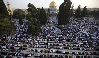 FILE - In this June 5, 2019 file photo, Palestinians pray in front of the Dome of the Rock shrine on the start of Eid al-Fitr holiday, in Jerusalem. Israeli police said they arrested the Palestinian minister of Jerusalem affairs early Wednesday, Sept. 25, 2019, for conducting political activity in east Jerusalem. Fadi al-Hadami is charged with allegedly breaking a law prohibiting political activity in Jerusalem by the Palestinian Authority, which is based in the Israeli-occupied West Bank. (AP Photo/Mahmoud Illean, File)