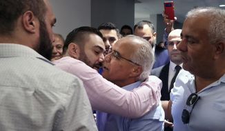 Mohammed Saleh, center, who was detained in Greece last week, is greeted by his son upon his arrival at the Rafik Hariri International Airport in Beirut, Lebanon, Wednesday, Sept. 25, 2019. Saleh, a Lebanese journalist who was mistakenly detained in Greece on suspicion of involvement in a 1985 TWA hijacking, arrived home in Lebanon. (AP Photo/Bilal Hussein)