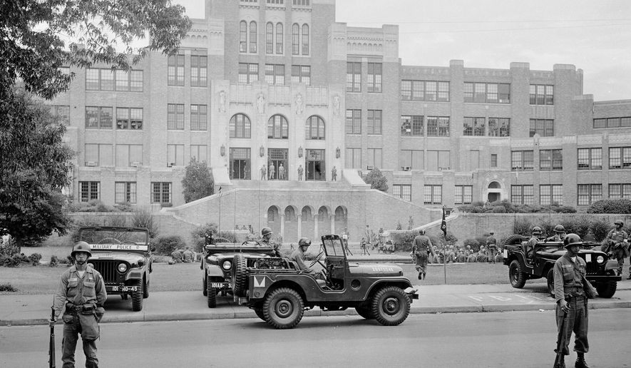 FILE - In this Sept. 26, 1957 file photo, members of the 101st Airborne Division take up positions outside Central High School in Little Rock, Ark. A plan to only grant Little Rock partial control of its schools is drawing complaints that the district may further segregate 62 years after nine black students were escorted into an all-white high school, and a push to end the local teachers union's bargaining power is stirring fears of even more instability. (AP Photo, File)