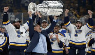 FILE - In this June 12, 2019, file photo, St. Louis Blues head coach Craig Berube carries the Stanley Cup after the Blues defeated the Boston Bruins in Game 7 of the NHL Stanley Cup Final, in Boston. The NHL 2019-20 regular season begins Oct. 2. (AP Photo/Michael Dwyer)