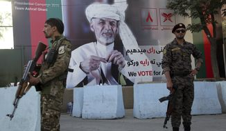 In this Monday, Sept. 23, 2019, photo, Afghan security forces stand guard in front of an election poster for presidential candidate Ashraf Ghani in Kabul, Afghanistan. Millions of Afghans are expected to go to the polls on Saturday to elect a new president, despite an upsurge of violence in the weeks since the collapse of a U.S.-Taliban deal to end Americas longest war, and the Taliban warning voters to say away from the polls. (AP Photo/Rahmat Gul)