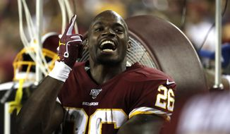 Washington Redskins running back Adrian Peterson talks to teammates on the bench during the first half of an NFL football game against the Chicago Bears Monday, Sept. 23, 2019, in Landover, Md. (AP Photo/Julio Cortez) **FILE**