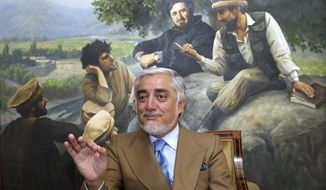 Abdullah Abdullah, a candidate in Afghanistan's upcoming presidential election speaks during an interview at his home, in Kabul, Afghanistan, Thursday, Sept. 26, 2019. Abdullah Abdullah, a leading contender in this weekend's presidential election, is alleging widespread abuses of power by his rival, incumbent President Ashraf Ghani. The painting behind Abdullah shows him with Ahmad Shah Masood, a hero to some in Afghanistan, who was killed in an al Qaida suicide bombing on Sept. 9, 2001, just two days before Al Qaida terrorists attacked the United States killing nearly 3,000 people. (AP Photo/Ebrahim Noroozi)