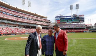 Cincinnati Reds announcer Marty Brennaman, center, stands with Reds owner Bob Castellini, left, and Phil Castellini, right, before a baseball game against the Milwaukee Brewers, Thursday, Sept. 26, 2019, in Cincinnati. The 77-year-old broadcaster is retiring after 46 years. (AP Photo/John Minchillo)