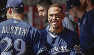 Milwaukee Brewers' Orlando Arcia, right, celebrates in the dugout after scoring on an RBI double by Ben Gamel off Cincinnati Reds starting pitcher Luis Castillo in the fourth inning of a baseball game, Thursday, Sept. 26, 2019, in Cincinnati. (AP Photo/John Minchillo)