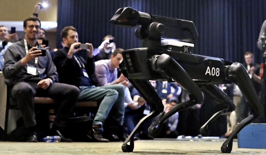 FILE - In this May 24, 2018, file photo, a Boston Dynamics SpotMini robot is walks through a conference room during a robotics summit in Boston. The Cirque du Soleil Entertainment Group says it's in talks with robot-maker Boston Dynamics about using the four-legged Spot robot in its live shows. (AP Photo/Charles Krupa, File)