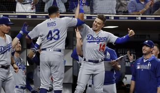 Los Angeles Dodgers' Edwin Rios (43) is greeted by teammate Enrique Hernandez (14) after hitting a home run during the seventh inning of the team's baseball game against the San Diego Padres on Wednesday, Sept. 25, 2019, in San Diego. (AP Photo/Gregory Bull)