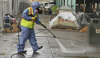 FILE - In this Feb. 26, 2016 file photo, a city worker uses a power washer to clean the sidewalk by a tent city along Division Street in San Francisco. The U.S. Environmental Protection Agency says California is falling short on preventing water pollution, largely because of its problem with homelessness in cities such as Los Angeles and San Francisco. EPA Administrator Andrew Wheeler outlined the complaints Thursday, Sept. 26, 2019 in a letter to California Gov. Gavin Newsom. (AP Photo/Eric Risberg, File)
