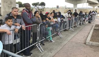 "Asylum seekers in Tijuana, Mexico, listen to names being called from a waiting list to claim asylum at a border crossing in San Diego Thursday, Sept. 26, 2019. The Trump administration played ""bait and switch"" by instructing migrants to wait in Mexico for an opportunity to apply for asylum before imposing sharp restrictions on eligibility, attorneys said in a court filing Thursday. (AP Photo/Elliot Spagat)"