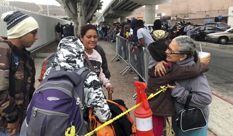 "Luz Bertila Zazueta, 75, of Tijuana, right, hugs farewell to a Peruvian woman and her four children whose numbers were called, Thursday, Sept. 26, 2019, to claim asylum at a border crossing in San Diego. Zazueta persuaded a neighbor to let the family live in his empty house for free during their six-month wait in Tijuana. The Trump administration played ""bait and switch"" by instructing migrants to wait in Mexico for an opportunity to apply for asylum before imposing sharp restrictions on eligibility, attorneys said in a court filing Thursday. (AP Photo/Elliot Spagat)"