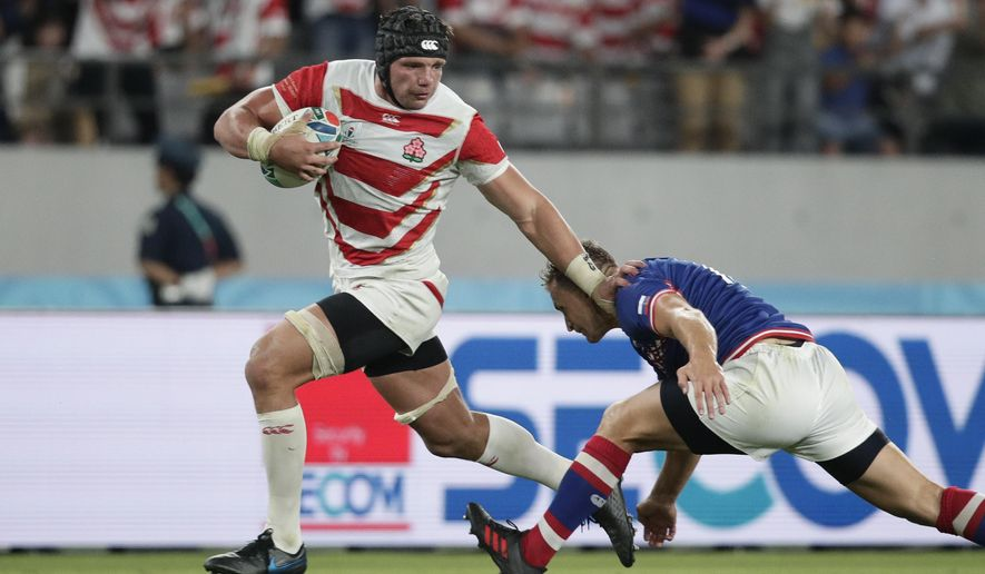 Japan's Pieter Labuschagne, left, fends off Russia's Yury Kushnarev on his way to scoring a try during the Rugby World Cup Pool A game at Tokyo Stadium in Tokyo, Friday, Sept. 20, 2019. (AP Photo/Jae Hong)