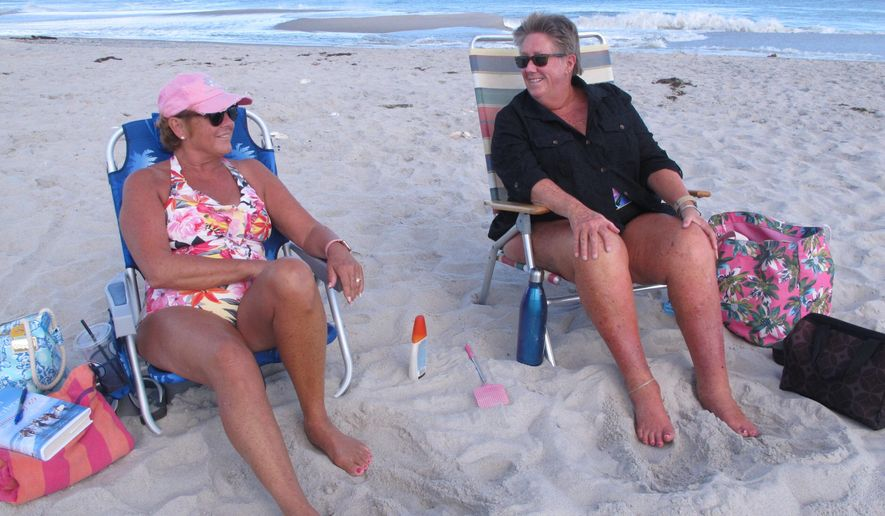 """In this Tuesday, Sept. 24, 2019 photo, Jam McLachlan, left, and Wendy Halliwell, right, enjoy a 77-degree day in Point Pleasant Beach, N.J., during a relaxed, uncrowded post-Labor Day period many at the Jersey shore refer to as """"Locals' Summer."""" (AP Photo/Wayne Parry)"""