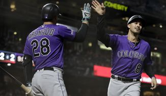 Colorado Rockies' Josh Fuentes, right, celebrates with Nolan Arenado (28) after scoring against the San Francisco Giants during the seventh inning of a baseball game Wednesday, Sept. 25, 2019, in San Francisco. (AP Photo/Ben Margot)