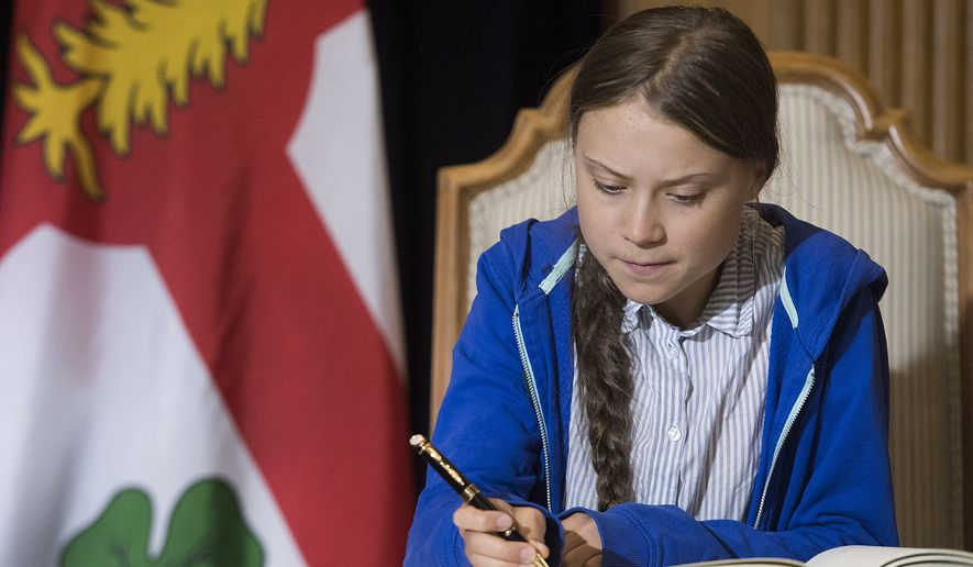 Swedish climate activist Greta Thunberg signs Montreal's Golden Book during a ceremony in Montreal, Friday, Sept. 27, 2019. (Graham Hughes/The Canadian Press via AP)