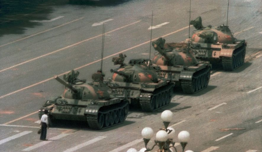 A Chinese man stands alone to block a line of tanks heading east on Beijing's Cangan Blvd. in Tiananmen Square, June 5, 1989. The man, calling for an end to the recent violence and bloodshed against pro-democracy demonstrators, was pulled away by bystanders, and the tanks continued on their way. Thousands of students demonstrated for democracy in Tiananmen Square. Hundreds died when the government sent in troops. (AP Photo/Jeff Widener) ** FILE **