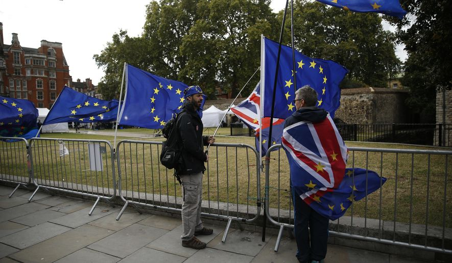 Anti-Brexit protesters demonstrate across the street from the Houses of Parliament in London, Thursday, Sept. 26, 2019. British Prime Minister Boris Johnson faced a backlash from furious lawmakers Thursday over his use of charged and confrontational language in Parliament about opponents of his Brexit plan. (AP Photo/Matt Dunham)
