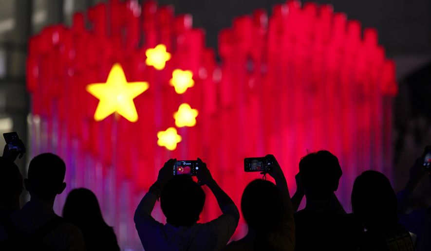 Visitors take photos with their smartphones of an installation depicting a heart-shaped Chinese national flag in Shanghai, China, Friday, Sept. 27, 2019. China marked its 70th anniversary on Oct. 1, 2019. (AP Photo) ** FILE **