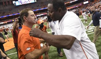 Clemson coach Dabo Swinney, left, and Syracuse coach Dino Babers congratulate each other after an NCAA college football game Saturday, Sept. 14, 2019, in Syracuse, N.Y. (AP Photo/Steve Jacobs)