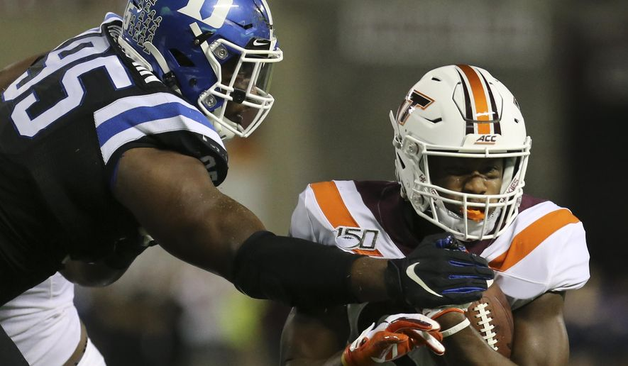 Virginia Tech's James Mitchell (82) is stopped at the 2-yard line by Duke defender Trevon McSwain (95) in the first quarter of an NCAA college football game, Friday, Sept. 27, 2019, in Blacksburg, Va. (Matt Gentry/The Roanoke Times via AP) **FILE**