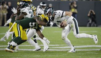 Philadelphia Eagles quarterback Carson Wentz scrambles to break free from the defense of Green Bay Packers outside linebacker Za'Darius Smith during the first half of an NFL football game Thursday, Sept. 26, 2019, in Green Bay, Wis. (AP Photo/Mike Roemer)