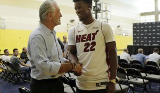 Miami Heat guard Jimmy Butler (22) shakes hands with Miami Heat President Pat Riley, left, following an NBA basketball news conference, Friday, Sept. 27, 2019, in Miami. Butler spoke publicly for the first time since the July trade that brought him to South Florida as the new face of the franchise. (AP Photo/Lynne Sladky)
