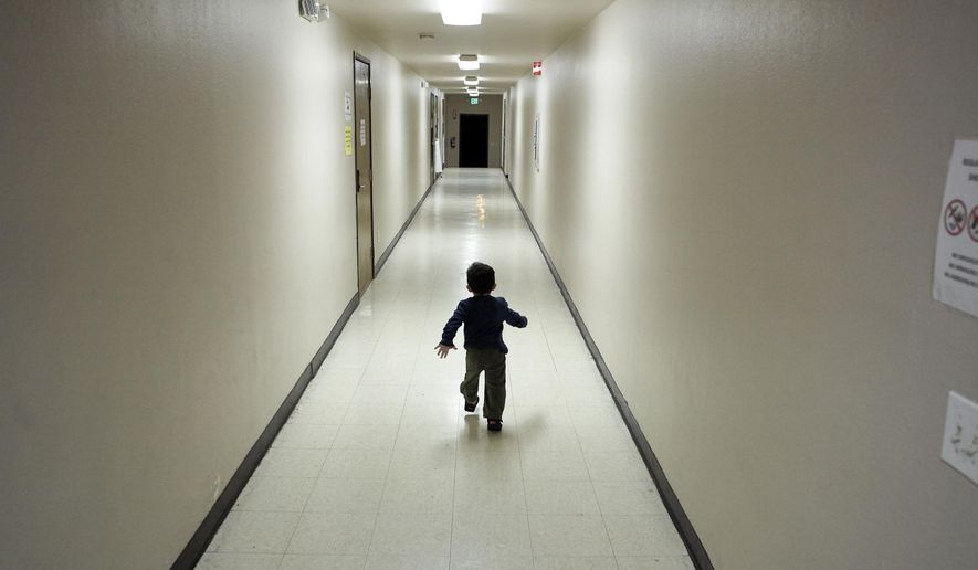 FILE - In this Dec. 11, 2018 file photo, an asylum-seeking boy from Central America runs down a hallway after arriving from an immigration detention center to a shelter in San Diego. The Trump administration will make a case in court to end a longstanding settlement governing detention conditions for immigrant children, including how long they can be held by the government. A hearing is scheduled before a federal judge Friday, Sept. 27, 2019, in Los Angeles over the so-called Flores settlement. (AP Photo/Gregory Bull, File)