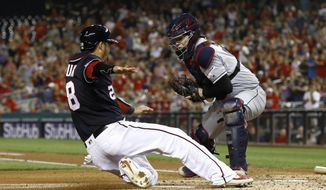 Washington Nationals' Kurt Suzuki, left, slides past Cleveland Indians catcher Roberto Perez for a run on Gerardo Parra's double in the second inning of a baseball game, Friday, Sept. 27, 2019, in Washington. (AP Photo/Patrick Semansky)