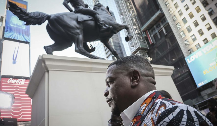 "Visual artist Kehinde Wiley, best known for his portrayals of contemporary African-American and African-Diasporic individuals, appears at the unveiling his first monumental public sculpture ""Rumors of War,"" an equestrian portraiture of warfare and heroism, Friday Sept. 27, 2019, in New York. The work will be exhibited in Times Square through December 1.  (AP Photo/Bebeto Matthews)"