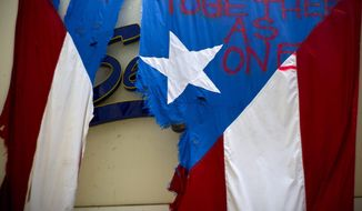 """FILE - In this Sept. 27, 2017 file photo,  a ripped Puerto Rican national flag spray painted with the words """"Together as One"""" hangs from the facade of a business, in San Juan, Puerto Rico. A federal control board that oversees Puerto Rico's finances filed in court Friday, Sept. 27, 2019, a long-awaited plan that it says would reduce the U.S. territory's debt by more than 60 percent and pull the island out of bankruptcy in what government officials called a historic moment. (AP Photo/Ramon Espinosa)"""