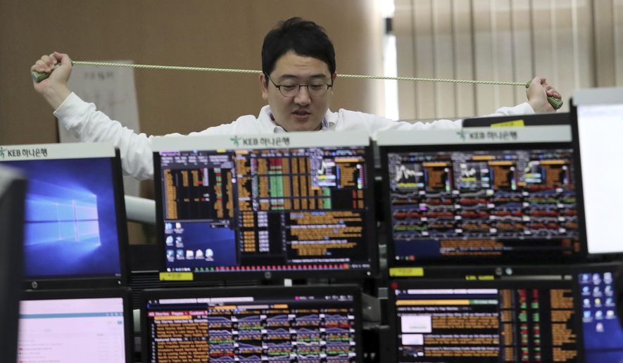 A currency trader stretches at the foreign exchange dealing room of the KEB Hana Bank headquarters in Seoul, South Korea, Friday, Sept. 27, 2019. Asian stocks were mixed Friday as traders weighed data showing slower U.S. economic growth and the possible impact of an impeachment inquiry of President Donald Trump. (AP Photo/Ahn Young-joon)