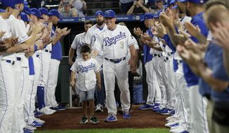 Kansas City Royals manager Ned Yost (3) walks his family between players during a ceremony before a baseball game against the Minnesota Twins at Kauffman Stadium in Kansas City, Mo., Friday, Sept. 27, 2019. Yost announced he will retire after Sunday's game. (AP Photo/Orlin Wagner)
