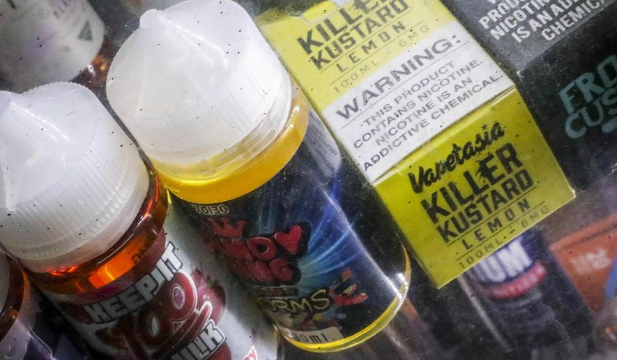 In this Sept. 16, 2019 file photo Flavored vaping solutions are shown in a window display at a vape and smoke shop in New York.  (AP Photo/Bebeto Matthews, File)  **FILE**