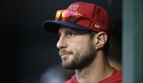 Washington Nationals' Max Scherzer stands in the dugout during a baseball game against the Cleveland Indians, Saturday, Sept. 28, 2019, in Washington. The Nationals won 10-7. (AP Photo/Nick Wass)