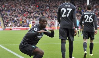 Liverpool's Georginio Wijnaldum, left, celebrates after scoring his side's opening goal during the English Premier League soccer match between Sheffield United and Liverpool at Bramall Lane in Sheffield, England, Saturday, Sept. 28, 2019. (AP Photo/Rui Vieira)