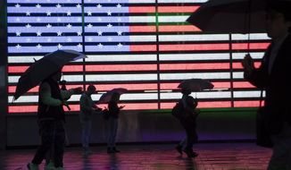 FILE - In this April 26, 2019, file photo, visitors to New York's Times Square use umbrellas to shield themselves against the rain as they walk past the Armed Forces Recruitment Center. The U.S. Census Bureau is creating tighter privacy controls in response to new fears that census questions could threaten the privacy of the people who answered them. (AP Photo/Mary Altaffer, File)